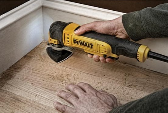 Corded oscillating multi-use tool sanding a wooden floor.