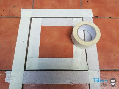 Applying masking tape around tile