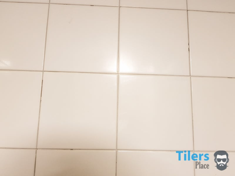 Bathroom tiles with all the grout removed with the use of a grout saw.