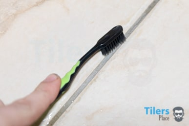 scrubbing grout with a tooth brush